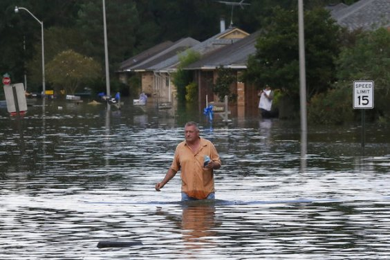 A man wades through a flooded street in Ascension Parish